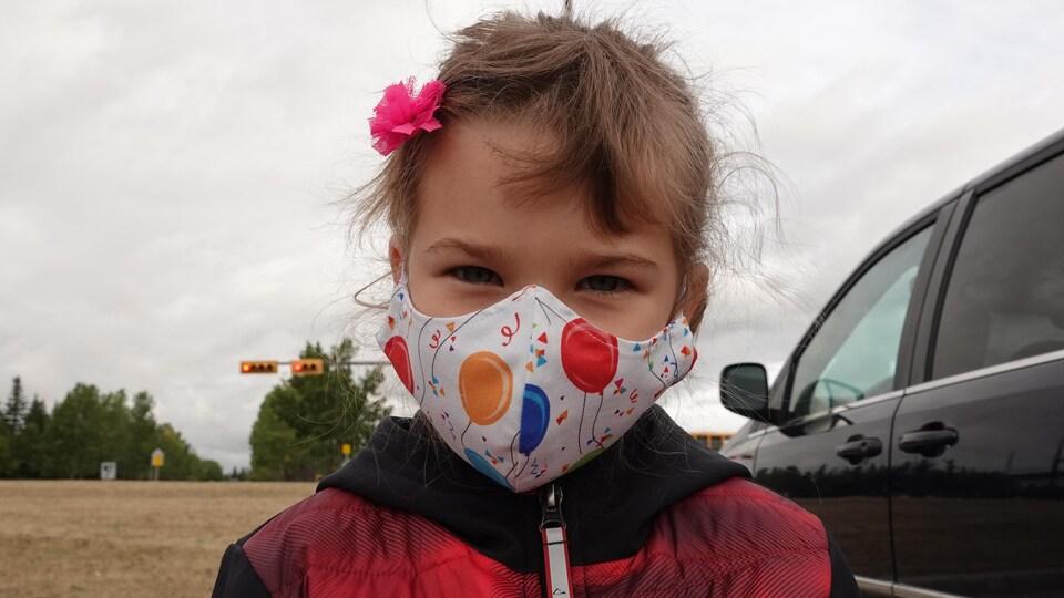 Une petite fille avec un masque coloré sur le visage.