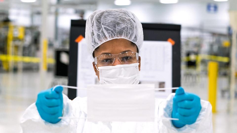 Une femme tient un masque chirurgical blanc.