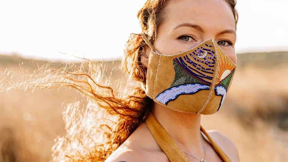 L'artiste crie de la Saskatchewan, Vanessa Hyggen, se tient debout dans un champ et porte son masque qui illustre d'un côté la nuit et de l'autre le jour qui se lève sur les Prairies canadiennes.