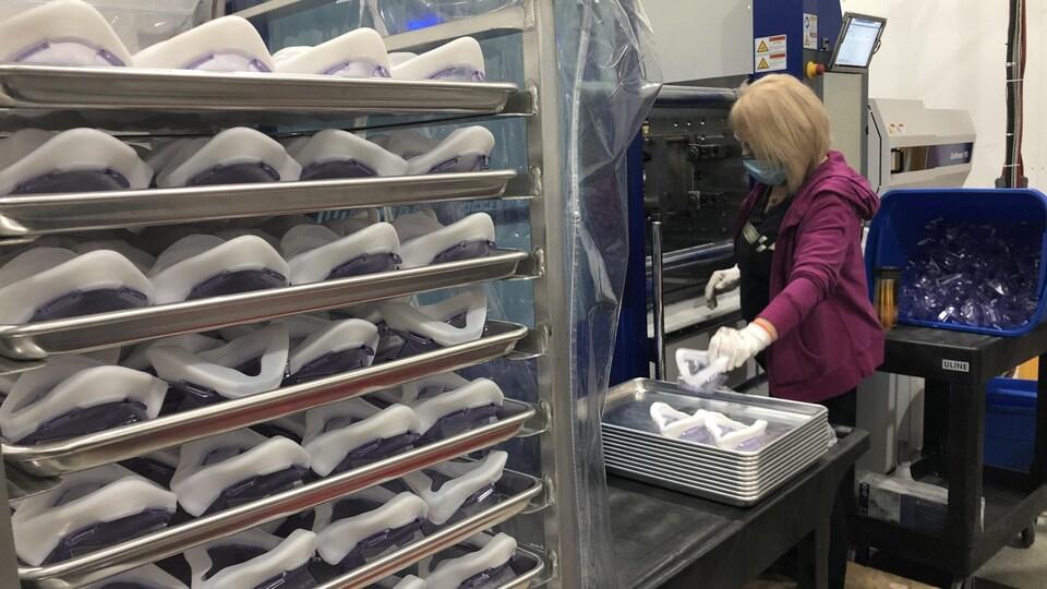 Une femme travaille à la fabrication de masques N99.