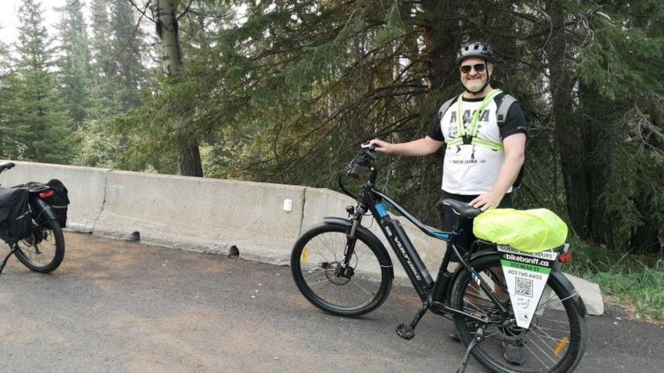 Maxime Lanciault pose pour une photo avec un vélo électrique.