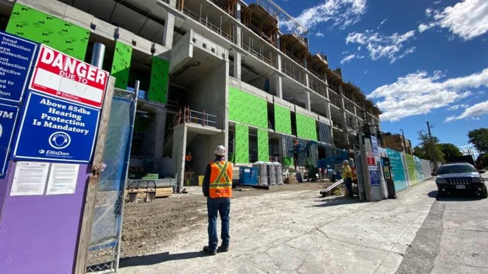 Un ouvrier du bâtiment regarde le chantier.