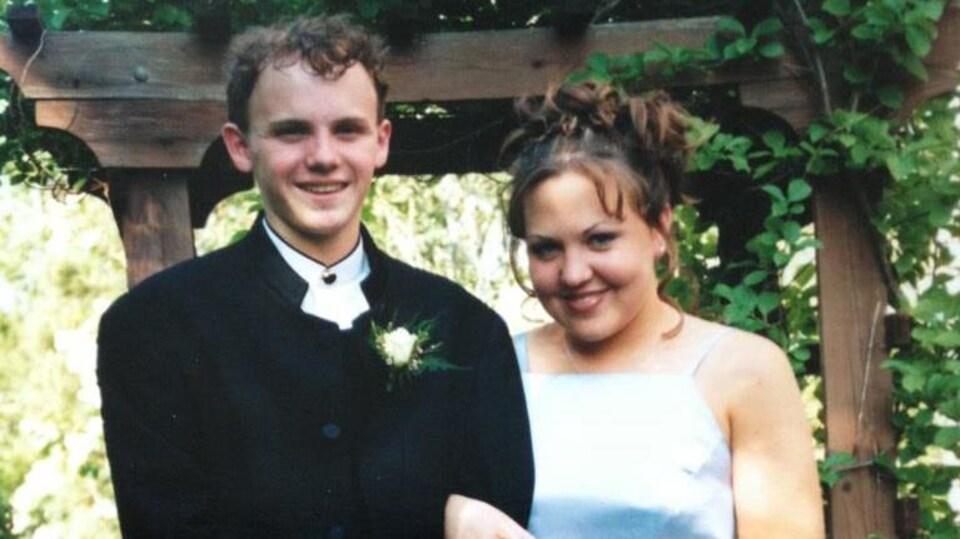Un garçon habillé d'un costume et une fille en robe de bal posent bras dessus, bras dessous devant une tonnelle fleurie.