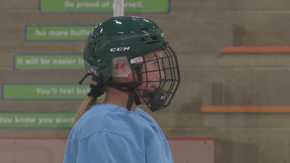 Mireille Martin est en tenue de hockey sur la glace. Elle regarde au loin, casque sur la tête.