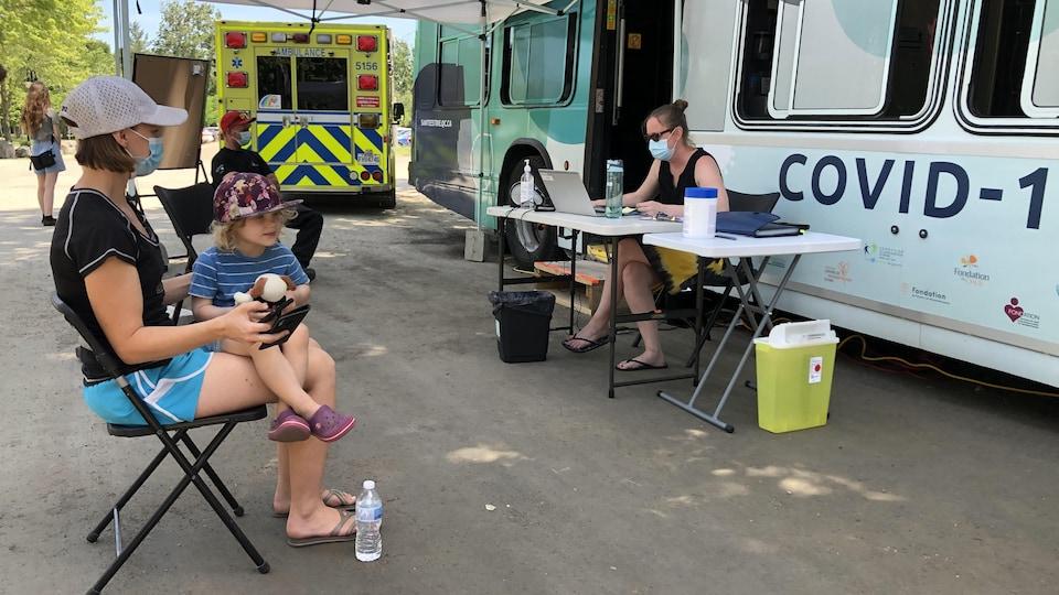 Une femme attend d'être vaccinée devant un autobus