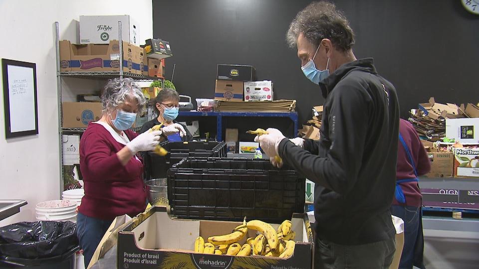 Trois bénévoles ouvrent des boîtes de nourriture, et en sortent notamment des bananes.