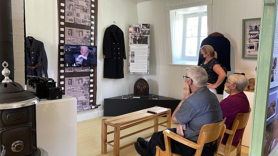 Trois personnes en train de regarder une vidéo dans l'exposition au moulin Paradis.
