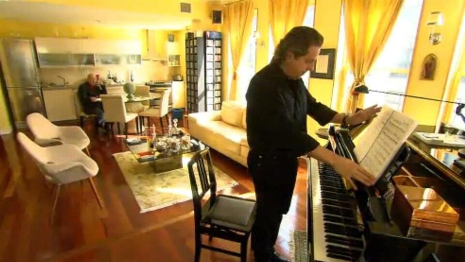 Un homme assis à une table de cuisine observe au loin un pianiste debout en train de lire une partition.