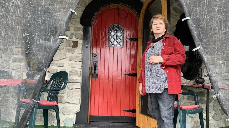 Nicole Larouche devant l'entrée de sa maison-château, à La Bostonnais.