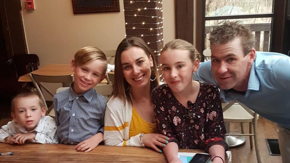 Une femme et un homme posent à un table en compagnie de trois enfants.