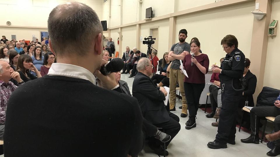 Une femme avec un micro s'adresse à une foule. Un homme de dos l'écoute aussi.
