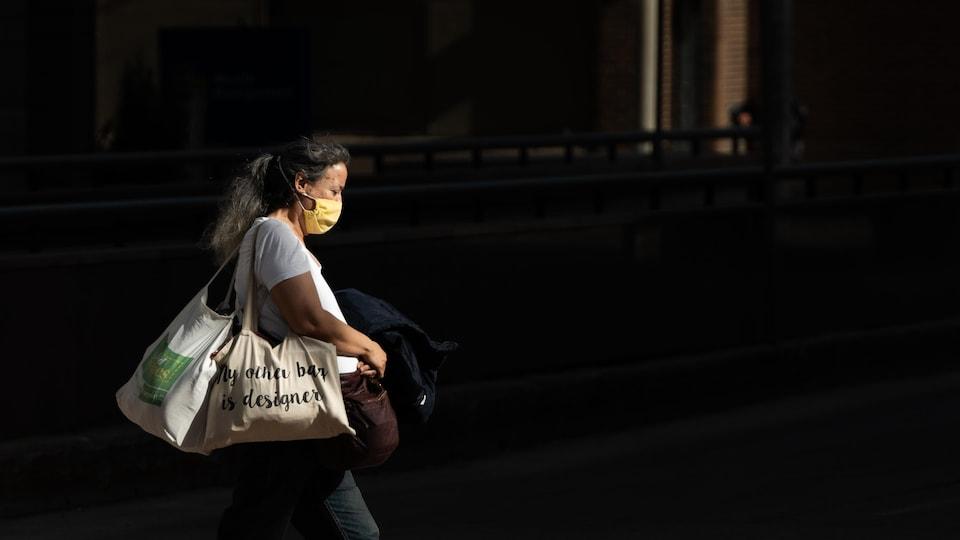 Une femme marche sur la rue Queen à Ottawa.