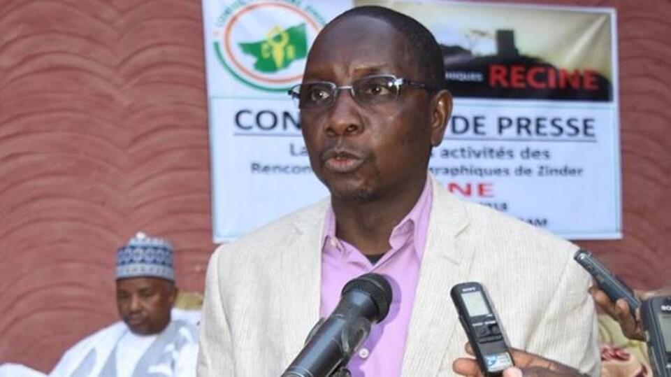 Ousmane Ilbo Mahamane en train de parler devant des micros pendant une conférence de presse.