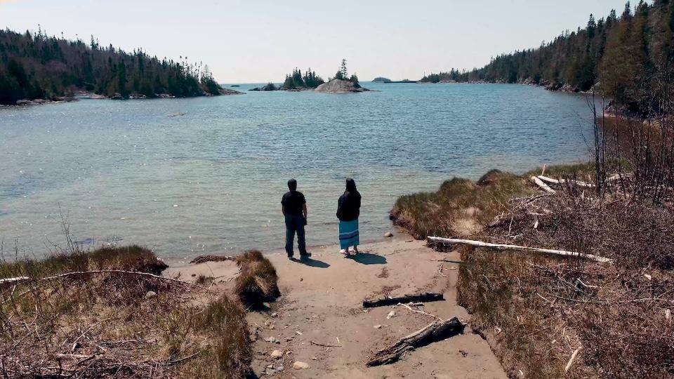 Un homme et une femme qui regarde un grand lac debout sur une plage.