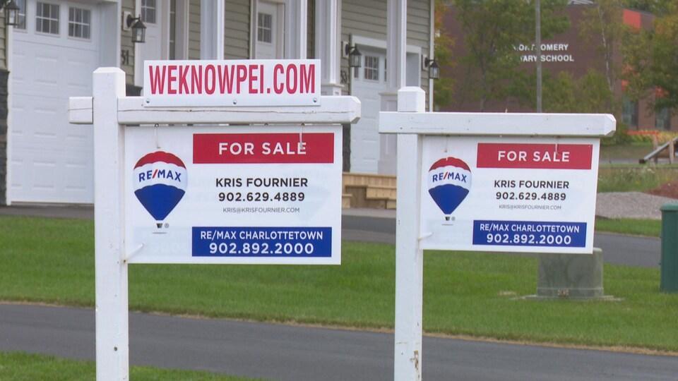 Deux panneaux à vendre sont disposés devant des maisons neuves.