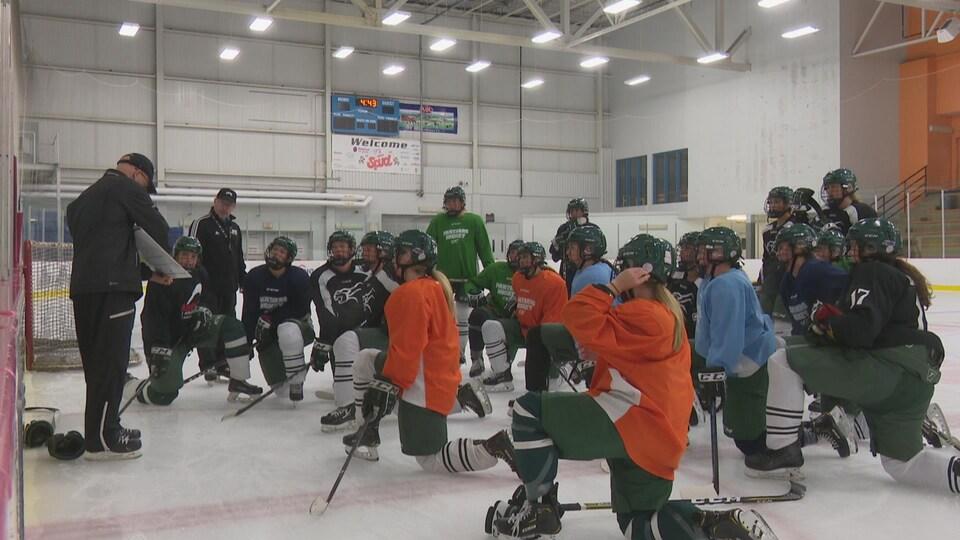 Les joueuses des Panthers de UPEI sont agenouillées sur la glace. Elles écoutent leur entraîneur donner les consignes du prochain exercice.