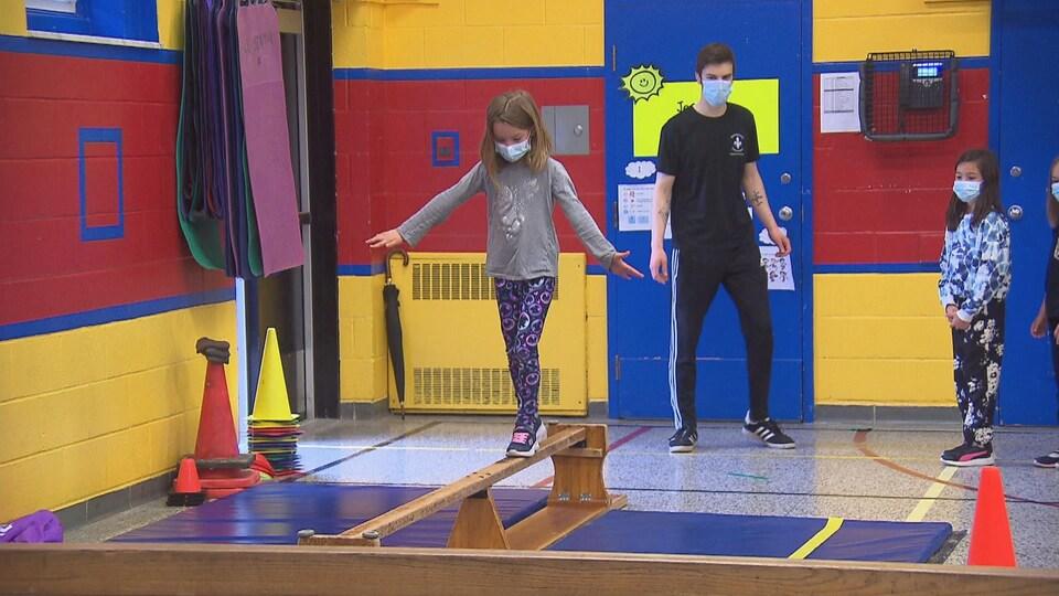 Une jeune fille marche sur une poutre en tentant de conserver son équilibre.