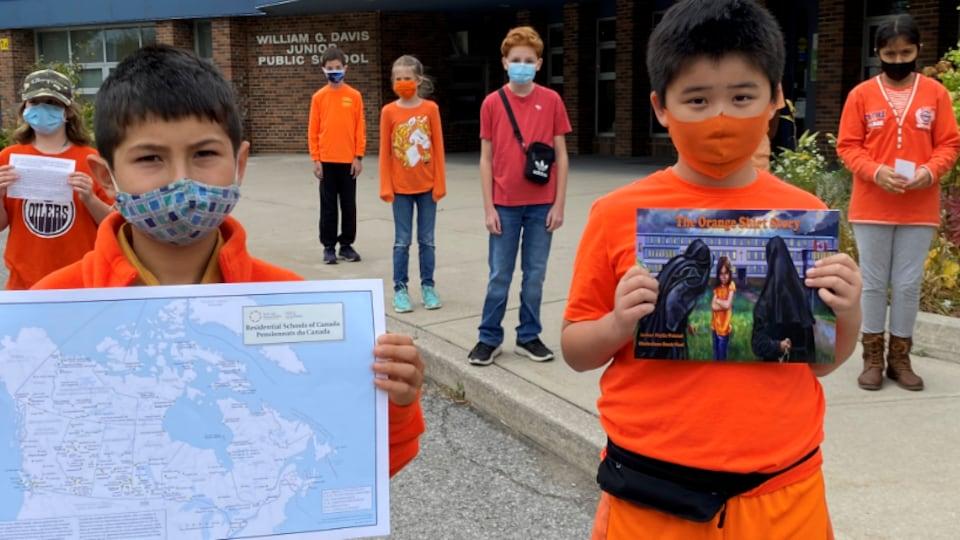 Des enfants aux vêtements de couleur orange tiennent une carte du Canada et des pancartes en souvenir des enfants autochtones disparus.