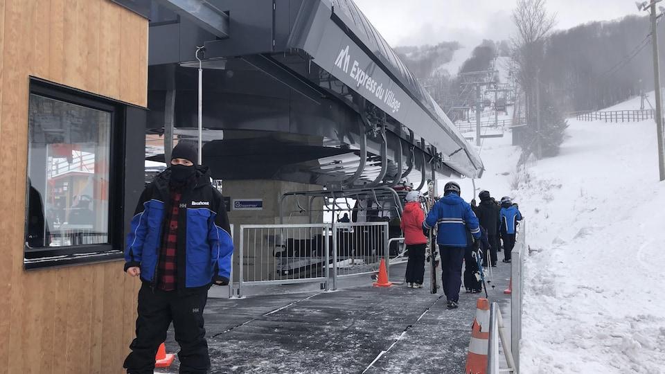 Des skieurs en attente à un remonte-pente.