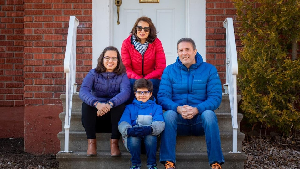 Une famille de quatre personnes est assise dans les marches de leur petit perron.