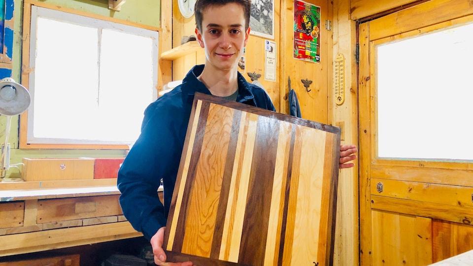 Sacha pose fièrement avec un plan de travail en bois pour la cuisine qu'il a conçu.