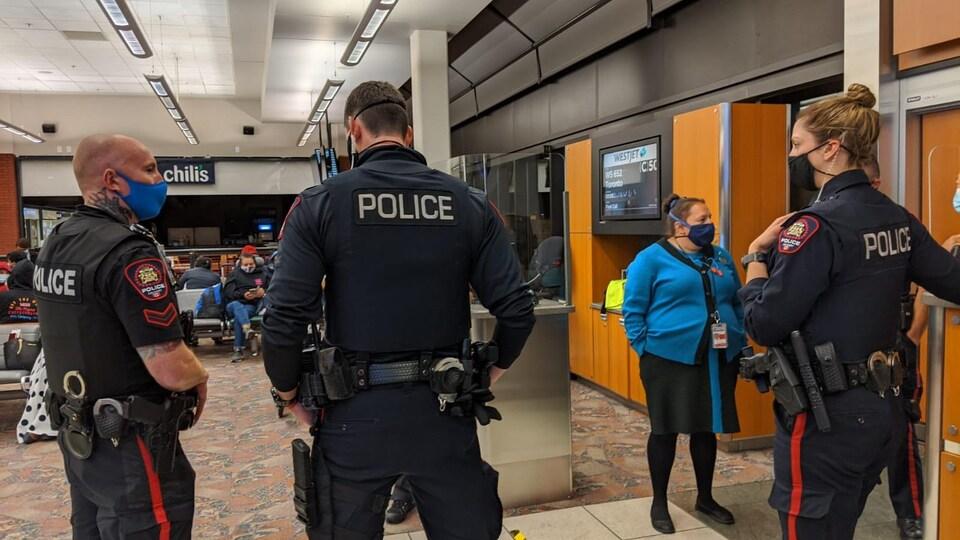 Des policiers se tiennent devant une porte d'embarquement à l'aéroport de Calgary.
