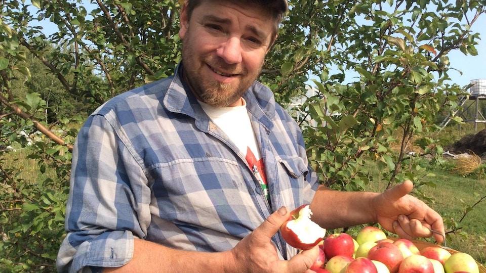 Aaron Shantz portant un panier de pommes.