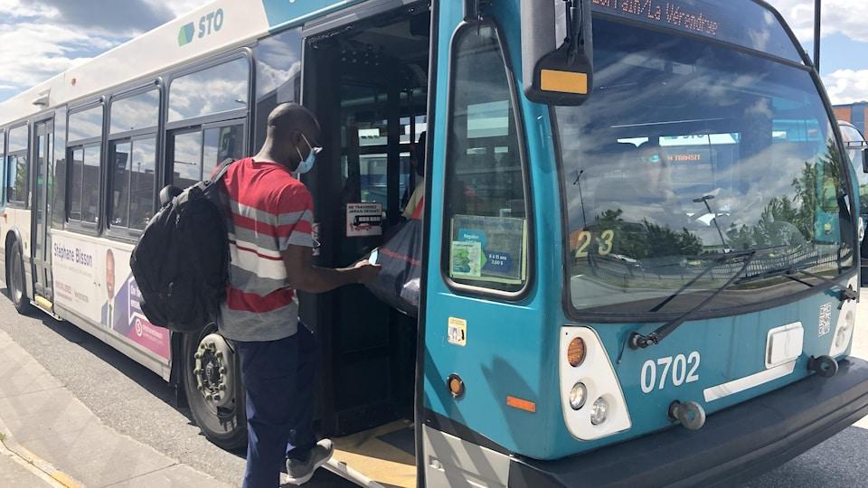 Un homme portant le masque qui monte à bord d'un autobus