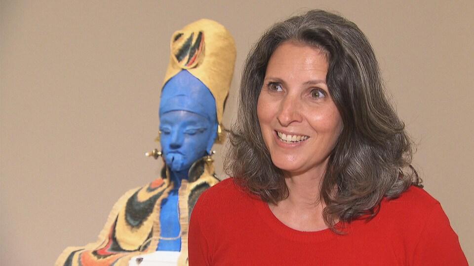 Josée Drouin-Brisebois, souriante, devant une sculpture.