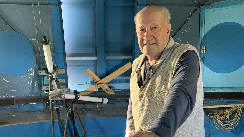 Le propriétaire actuel du terrain sur lequel est situé l'observatoire, Roger Hamelin, aux côtés des télescopes se trouvant dans la tête du hibou.