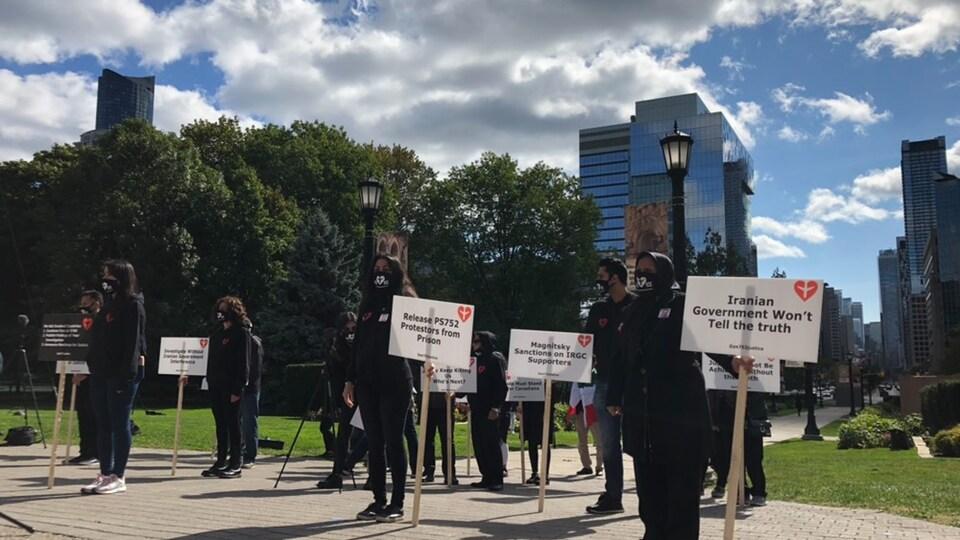 Plusieurs personnes vêtues de noir tiennent des écriteaux demandant la vérité autour de l'écrasement du vol PS752.