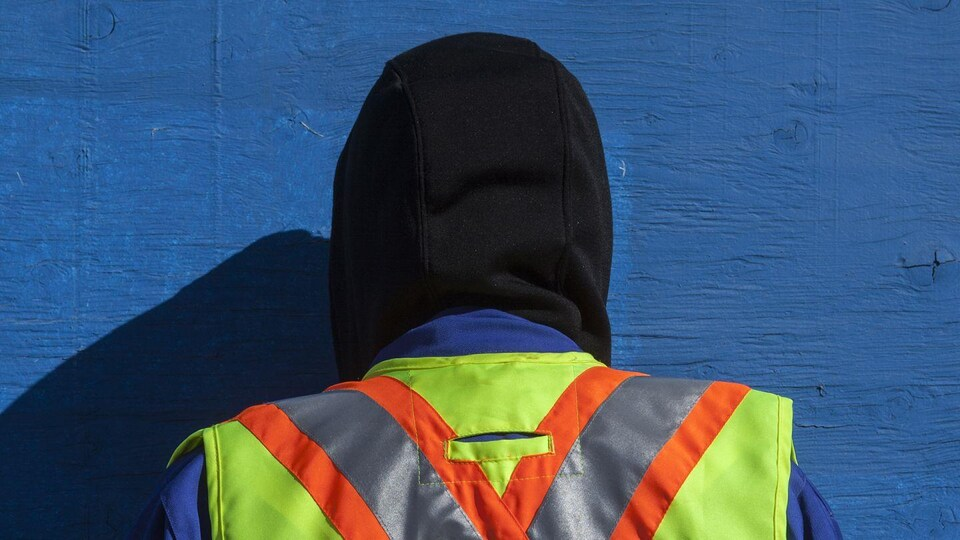 Personne de dos, avec un veste de visibilité. Face à cette personne un mur bleu.