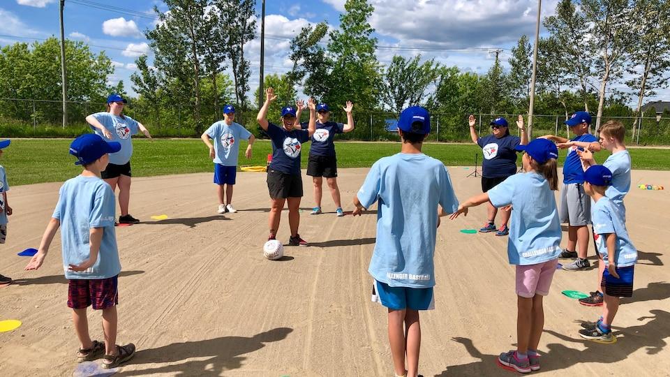 Les jeunes s'étirent sur le terrain de baseball.