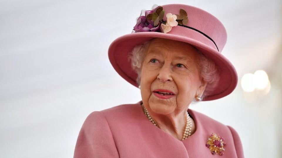 La reine regarde à sa droite. Elle porte un chapeau assorti à sa veste, où figurent une broche de fausses fleurs.
