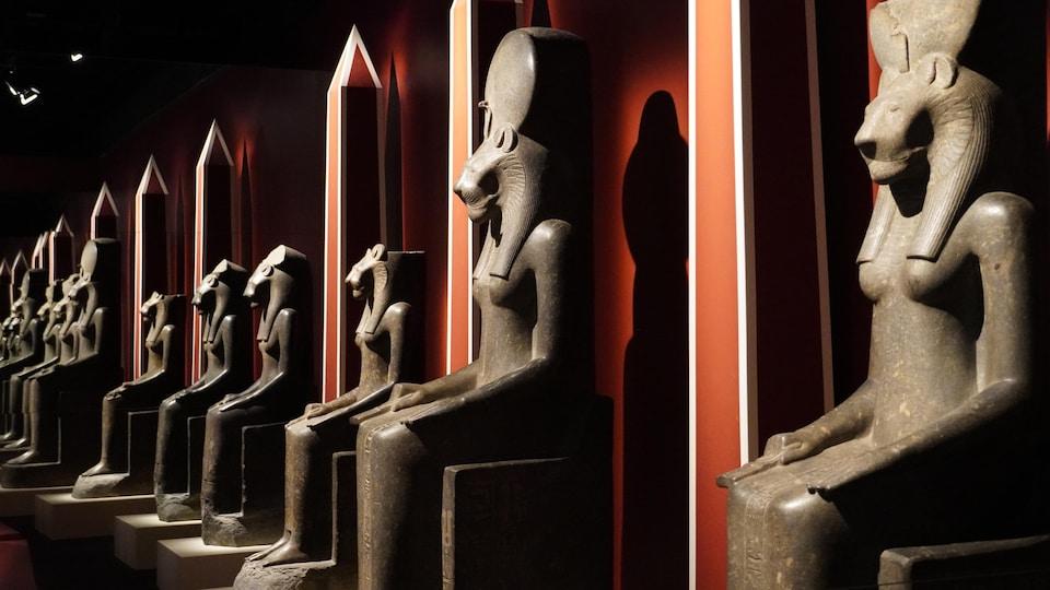 Plusieurs grandes statues égyptiennes le long d'un mur.