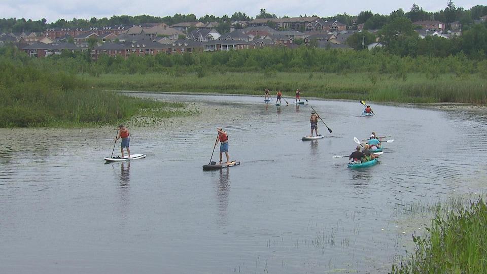 Des kayakistes et planchistes sur une rivière