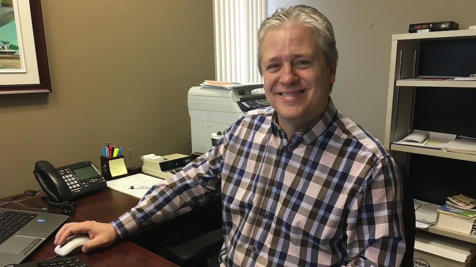 Un homme avec une chemise à carreau assis à son bureau en souriant.