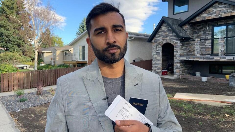 Safwan Choudhry tient un billet d'avion dans ses mains dans une rue résidentielle.