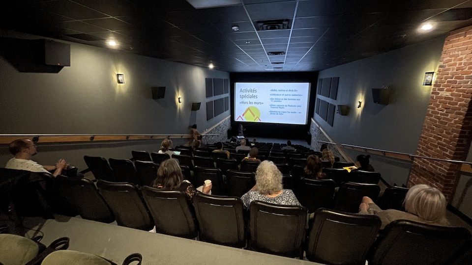 Une foule assise dans une salle de cinéma devant une présentation des activités offertes au Salon du livre de l'Estriere