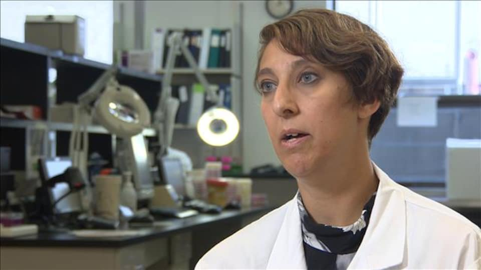 Une chercheuse en laboratoire regarde vers la gauche.
