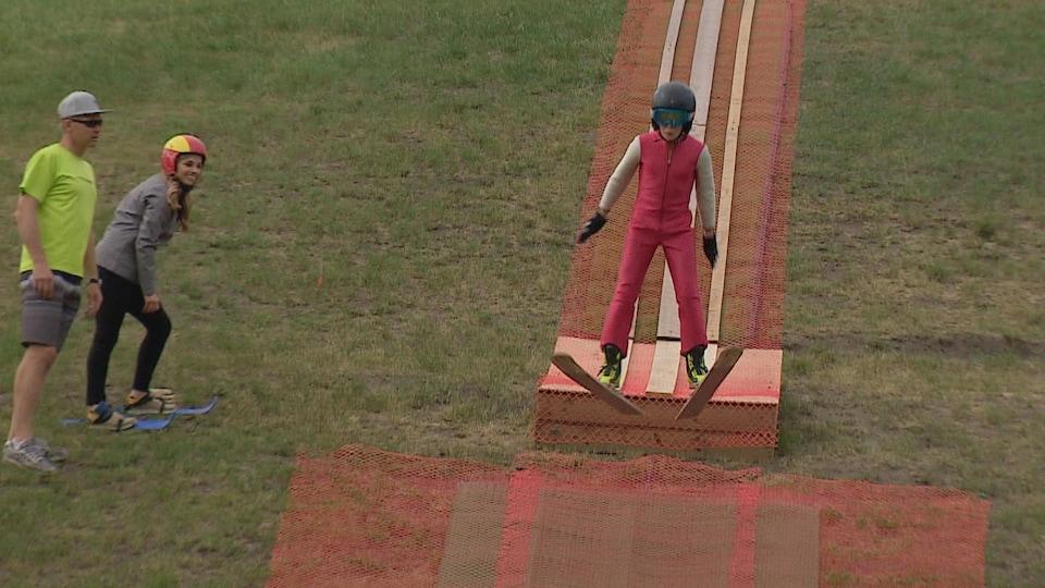 Un jeune saute sur une piste temporaire faite de plastique grillagé et de bouts de bois.