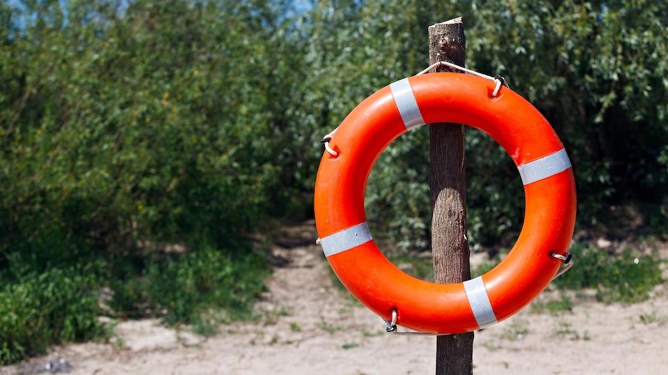 Une bouée de sauvetage accrochée sur un poteau de bois sur le bord d'une plage.