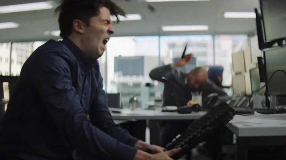 Un homme frappe un bureau avec un clavier.
