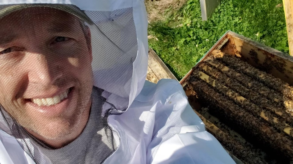 Scott MacFarlane debout devant une ruche d'abeilles.