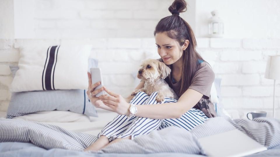 Une femme tient son chien sur elle alors qu'elle prend un égoportrait avec son téléphone intelligent.