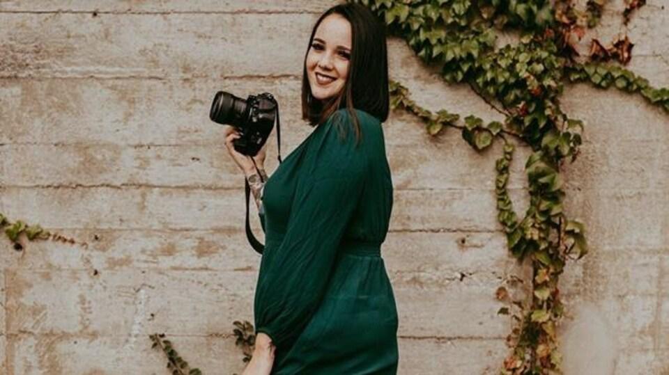 Une jeune femme tient une caméra et sourit.