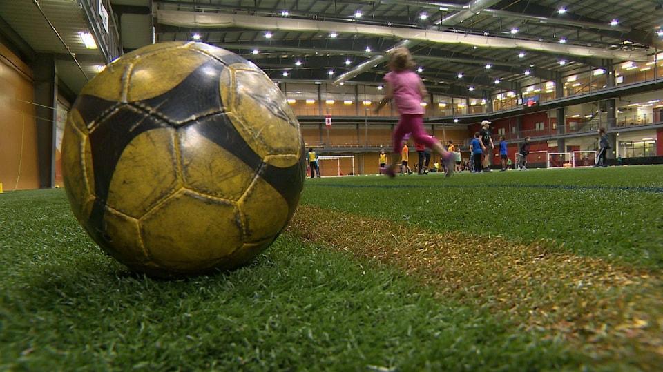 Un gros plan sur une balle de soccer dans un gymnase intérieur.
