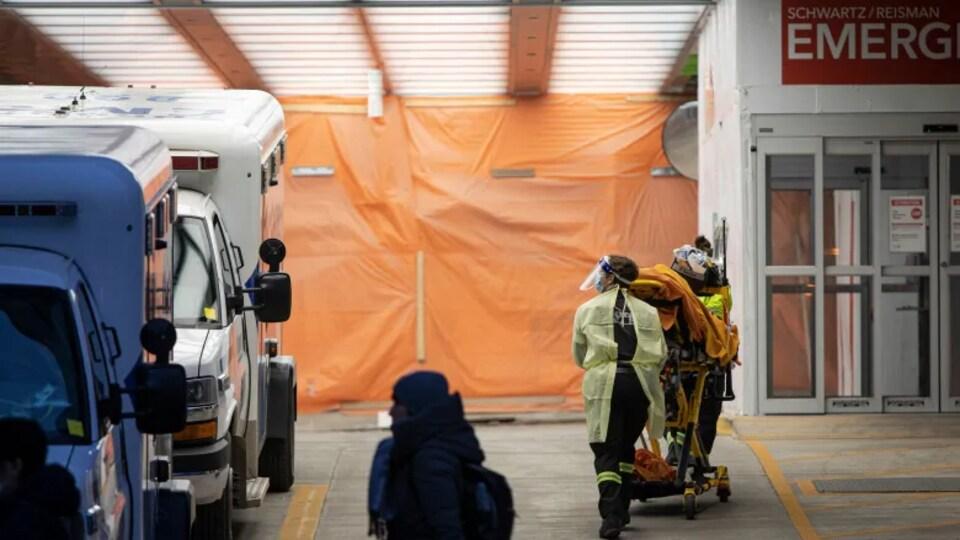 Du personnel médical transporte un patient installé dans un lit médical vers l'intérieur d'un hôpital.