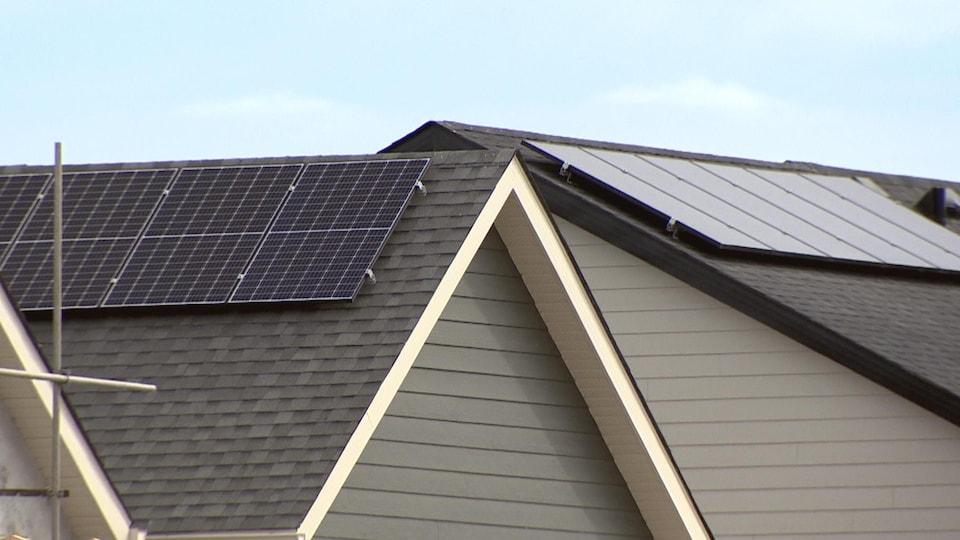 Des panneaux solaires sur le toit de deux maisons.