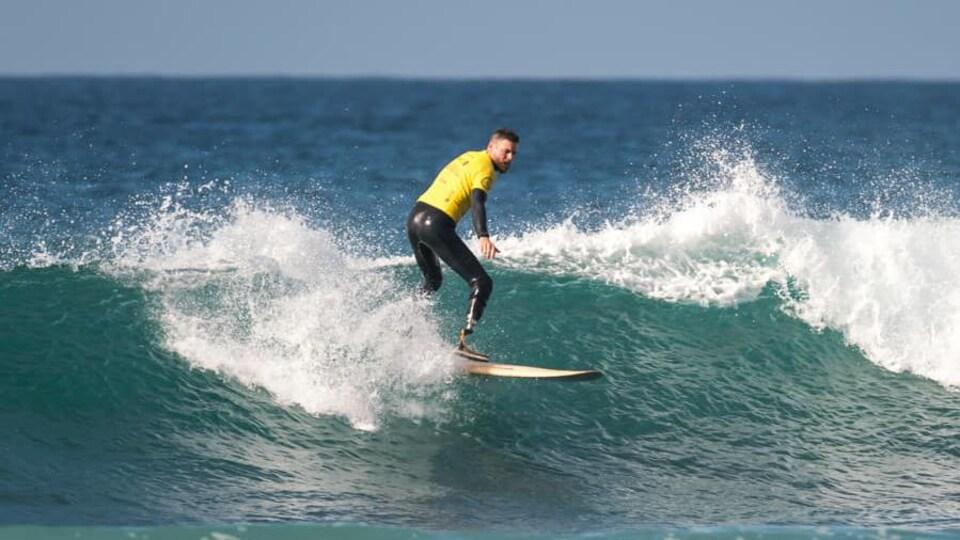 Muni d'une prothèse à la jambe droite, un homme file sur une vague sur son surf.